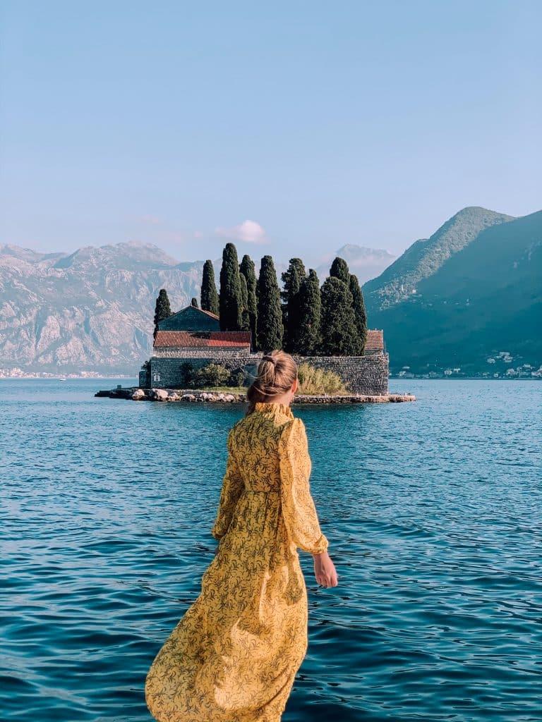 Kvinna i gul klänning med Saint George island i bakgrunden. Tagit ifrån our lady of the rocks