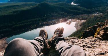 Vandringskängor hänger nedför berg med vacker utsikt i bakgrunden. Vila för att undvika skoskav.