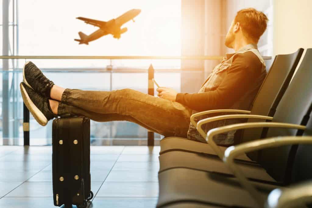 Man slappnar av och stressar inte på flygplats. Flygrädsla
