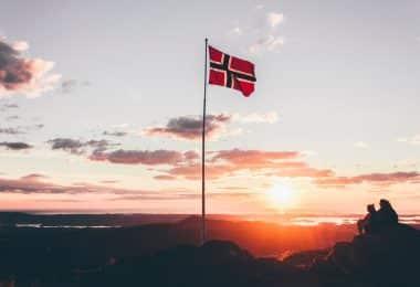 Norska flaggan på ett berg under vandring i Nordnorge